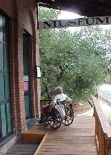 A visitor in a wheelchair uses the ramped entry to the Shasta Museum and Visitor Center.